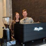 Chefin und Chef stehen hinter der neuen Kaffeemaschine.