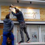 Zwei Männer bringen das Ladenschild über dem Eingang an.