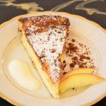Ein Stück kuchen auf einem Teller, angerichtet mit Sahne und Obst.