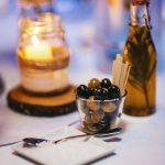 Oliven in einem Glas, eine kleine Glasflasche mit Olivenöl und ein Teller mit Salz.