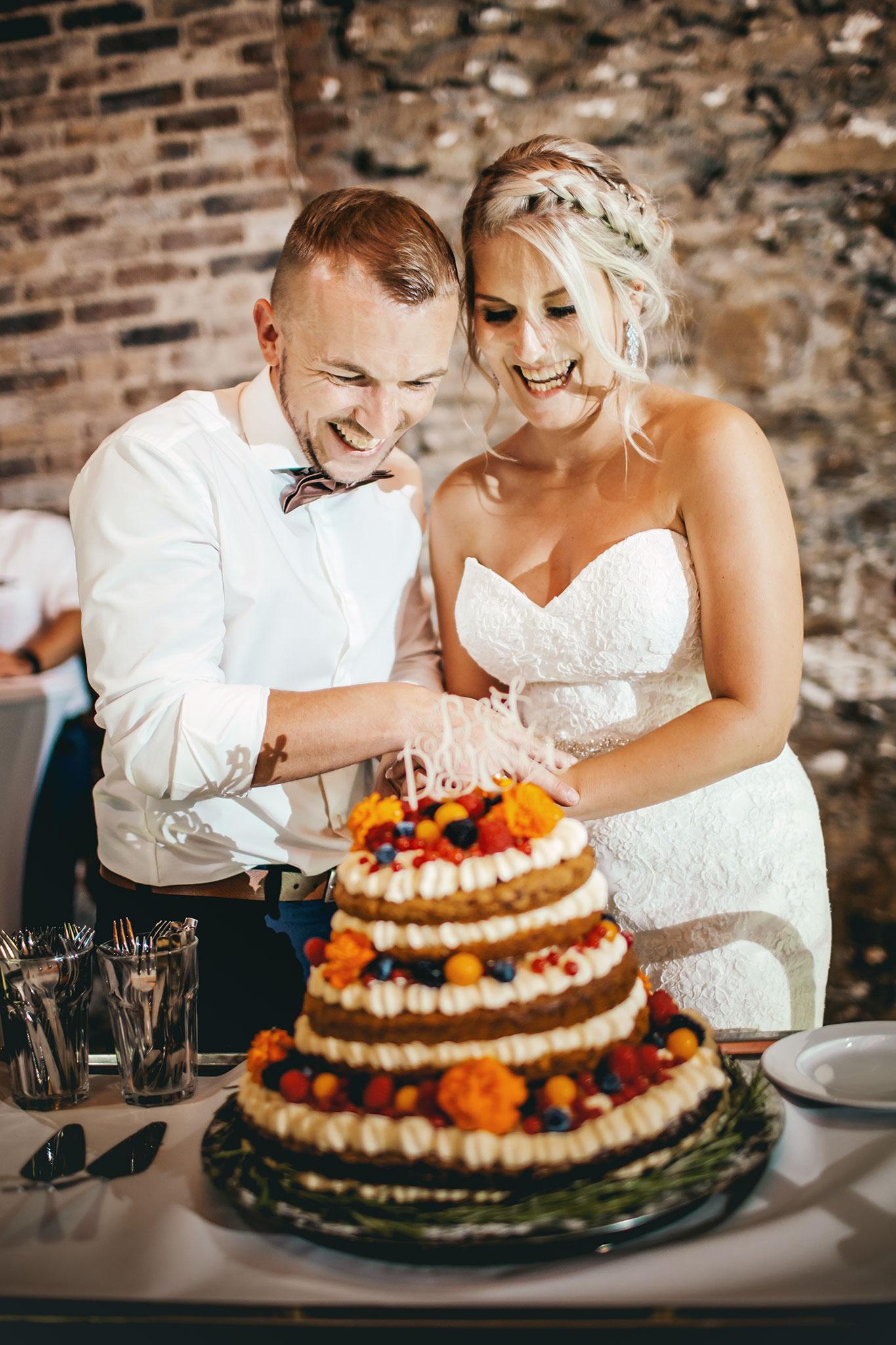 Das Bid zeigt ein Brautpaar beim Anschnitt ihrer Hochzeitstorte.