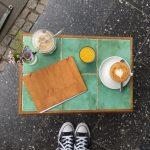 Ein kleiner Beistelltisch mit einem Cappuccino, der Karte und Blumen von oben fotografiert.