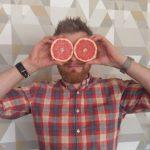 Chef steht vor der Wand und hält sich zwei Grapefruitscheiben vor die Augen.
