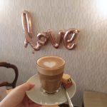 Ein Kaffee mit einem Herz vor einer Wand an der das Wort Love aus Luftballons hängt.