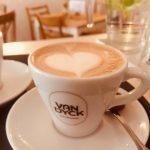 Ein Latteart-Herz, im Hintergrund sieht man das Cafe.