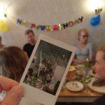 Ein Polaroidbild von einer Gebrutstagsgesellschaft, diese sitzt im Hintergrund und feiert.