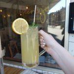 Eine Ztronenlimonade, im Hintergrund das Cafe.